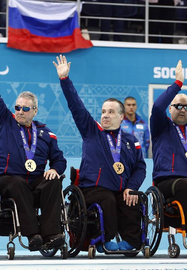 From left, Great Britain's Angie Malone, Jim Gault, Bob McPherson, Gregor Ewan, and Aileen Neilson celebrate after wining bronze medals after the wheelchair curling match between Great Britain and China at the 2014 Winter Paralympics in Sochi, Russia, Saturday, March 15, 2014. Great Britain won 7-3
