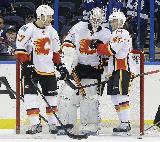 Calgary Flames goalie Karri Ramo, of Finland, center, celebrates with teammate Lance Bouma, left, and Chad Billins, right, after they defeated the Tampa Bay Lightning 4-1 during an NHL hockey game on Thursday, April 3, 2014, in Tampa, Fla