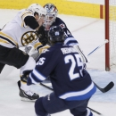 Boston Bruins' Brad Marchand (63) scores on Winnipeg Jets goaltender Michael Hutchinson (34) as Jets' Zach Redmond (25) watches during the first period of an NHL hockey game Thursday, April 10, 2014, in Winnipeg, Manitoba The Associated Press
