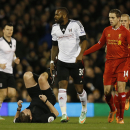 Referee Phil Dowd, second left, falls on his back after crashing into Fulham's Darren Bent, center, as Liverpool's Jordan Henderson, second right, and Martin Skrtel look on during their English Premier League soccer match at Craven Cottage, London, Wednes