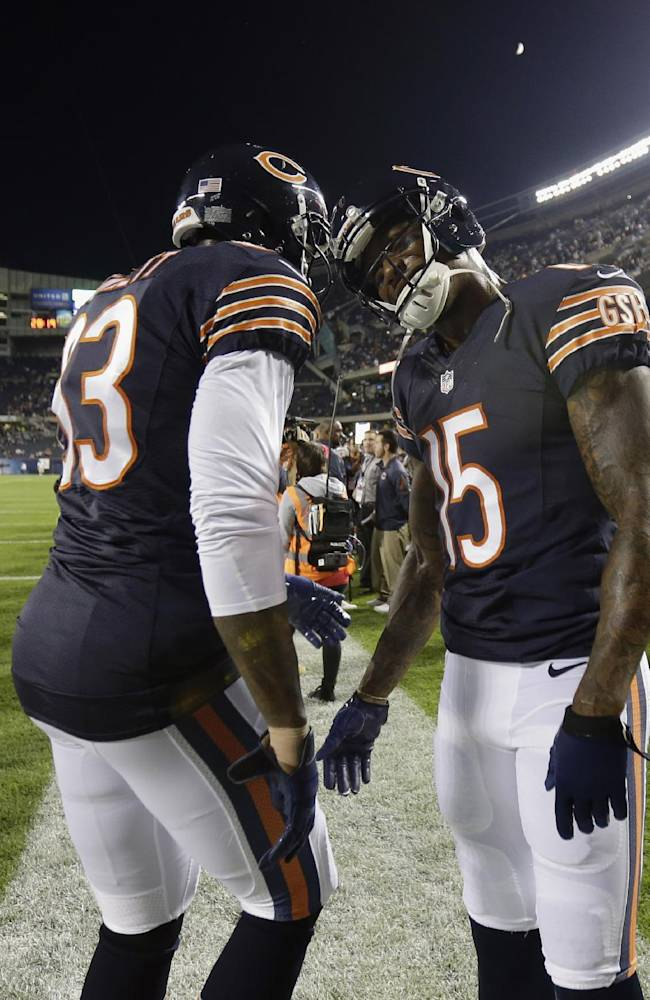 Chicago Bears tight end Martellus Bennett (83) and wide receiver Brandon Marshall (15) talk to each other before the Bears' NFL football game against the New York Giants, Thursday, Oct. 10, 2013, in Chicago