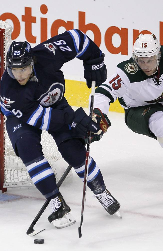 Minnesota Wild's Dany Heatley (15) chases down Winnipeg Jets' Zach Redmond (25) in front of Jets' goaltender Al Montoya (35) during first-period preseason NHL hockey game action in Winnipeg, Manitoba, Thursday, Sept. 19, 2013