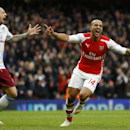 Arsenal's Theo Walcott, right, celebrates scoring a goal as Aston Villa's Alan Hutton shouts out during the English Premier League soccer match between Arsenal and Aston Villa at the Emirates stadium in London, Sunday, Feb. 1, 2015