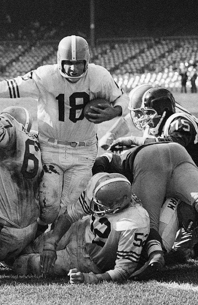 In this Sept. 30, 1962, file photo, Denver Broncos quarterback Frank Tripucka (18) drives through the New York Titans line standing up to score on a 1-yard touchdown in fourth quarter of American Football League game in New York. Denver linemen are guarding Bob McCullough (67) and center Jim Carton (52). Tripucka, who led Notre Dame to a 9-0-1 record and a No. 2 ranking in 1948, has died. He was 85. His son, Kelly Tripucka, a former Notre Dame basketball standout, said his father died of congestive heart failure at his home in Woodland Park, N.J