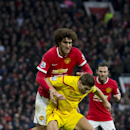 Manchester United's Marouane Fellaini, top, fights for the ball against Liverpool's Steven Gerrard during the English Premier League soccer match between Manchester United and Liverpool at Old Trafford Stadium, Manchester, England, Sunday Dec. 14, 2014