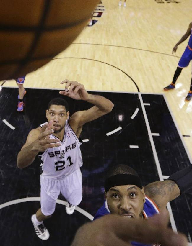 New York Knicks' Carmelo Anthony, front, reaches for rebound after San Antonio Spurs' Tim Duncan (21) missed his shot during the second half on an NBA basketball game, Thursday, Jan. 2, 2014, in San Antonio. New York won 105-101