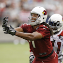 Arizona Cardinals' Larry Fitzgerald, left, has a pass slip off his fingertips as Antonio Cromartie defends during the first day of the NFL football team's training camp on Saturday, July 26, 2014, in Glendale, Ariz The Associated Press