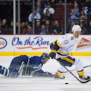 Vancouver Canucks' Alexander Edler, left, of Sweden, knocks the puck away from Nashville Predators' Olli Jokinen, of Finland, during the first period of an NHL hockey game in Vancouver, British Columbia, on Sunday, Nov. 2, 2014 The Associated Press