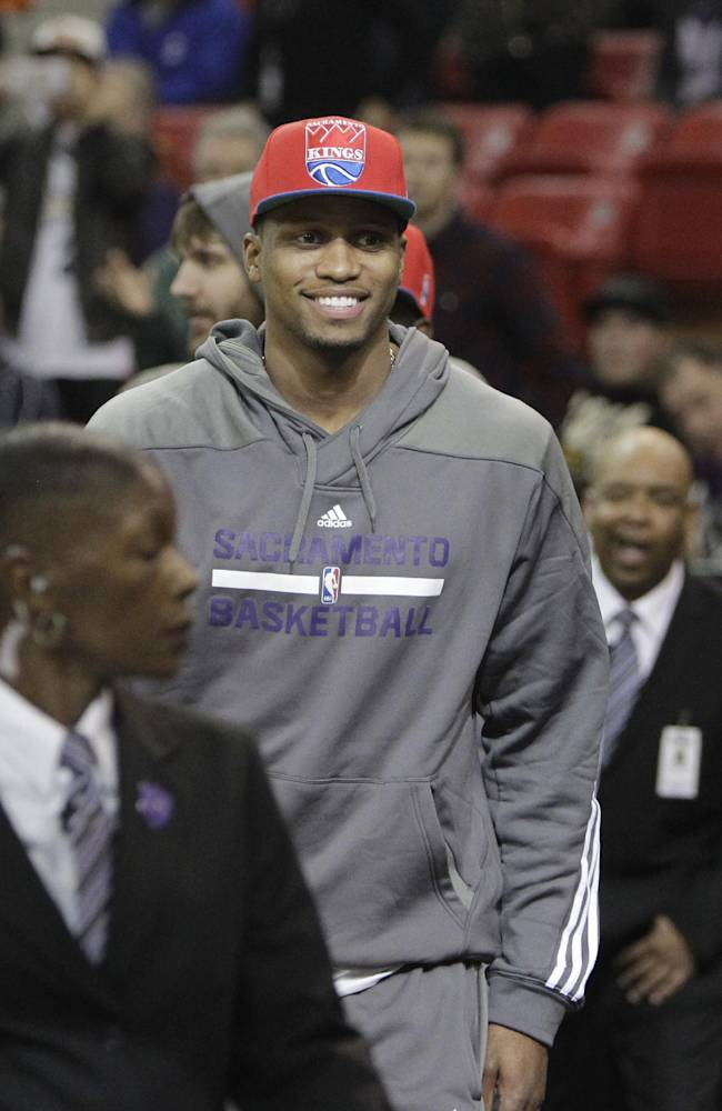Newly-acquired Sacramento Kings forward Rudy Gay smiles as he walks off the court during a timeout against the Dallas Mavericks in an NBA basketball game in Sacramento, Calif., Monday, Dec. 9, 2013.  The Kings sent four players to the Toronto Raptors in exchange for Gay, Quincy Acy and Aaron Gray. The Kings won 112-97