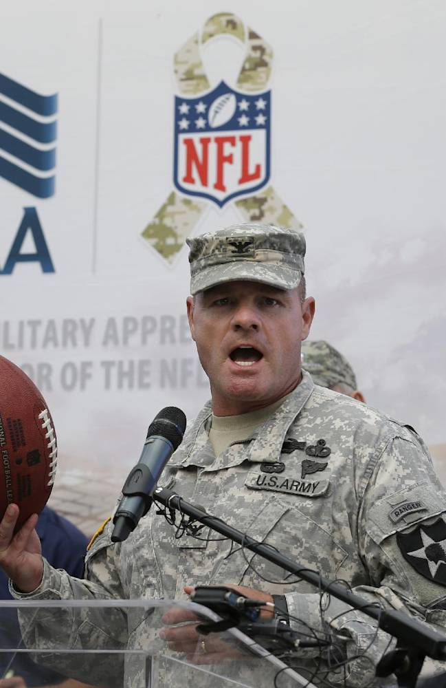 U.S. Army Col. Michael Getchell, commander of the 4th Stryker Brigade Combat Team at Joint Base Lewis-McChord, Wash., holds an NFL football given to him by the Seattle Seahawks, that his soldiers carried with them throughout their deployment to Afghanistan, during a ceremony Tuesday, Sept. 10, 2013. Players and other team officials were on hand to show their support for the military, and to officially name the U.S. Air Force 446th Airlift Wing as their