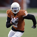 In this March 30, 2013 file photo, University of Texas football player Kendall Sanders (2) carries the ball during the team's spring football game in Austin, Texas. A University of Texas police spokeswoman says two Longhorns football players have been cha