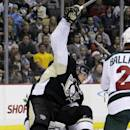 Pittsburgh Penguins' Sidney Crosby. top,collides with Minnesota Wild goalie Niklas Backstrom , bottom,during the second period of an NHL hockey game in Pittsburgh,2 Thursday, Dec. 19, 2013. Crosby was penalized for goaltender interference on the play. (AP Photo/Gene J. Puskar)