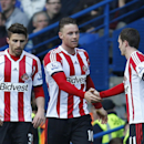 Sunderland's Connor Wickham, center, is congratulated by his teammates after scoring against Chelsea during their English Premier League soccer match at the Stamford Bridge ground in London, Saturday, April 19, 2014. Sunderland won the match 2-1
