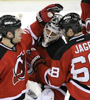 New Jersey Devils' Ryane Clowe, left, Cory Schneider and Jaromir Jagr (68) celebrate after the Devils defeated the Edmonton Oilers, 2-1 in overtime of an NHL hockey game, Friday, Feb. 7, 2014, in Newark, N.J. (AP Photo/Bill Kostroun)