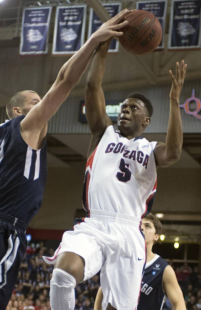 Gonzaga guard Gary Bell Jr. (5) takes a shot as San Diego forward Dennis Kramer (40) gets a hand on the ball during the first half of an NCAA college basketball game, Thursday, Jan. 23, 2014, at the McCarthey Athletic Center, in Spokane, Wash