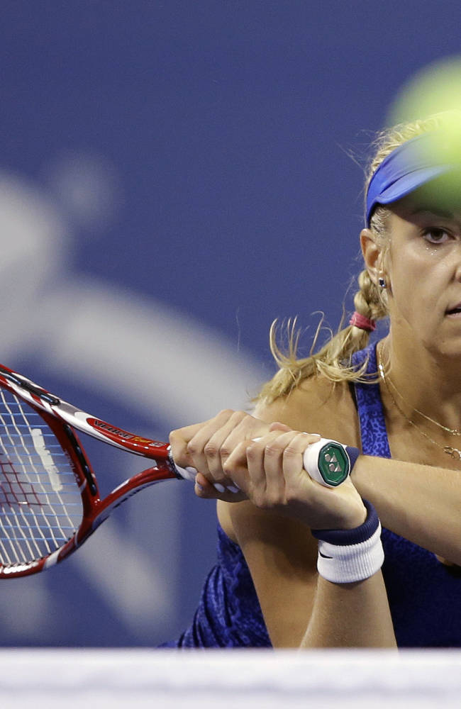 Sabine Lisicki, of Germany, returns a shot to Maria Sharapova, of Russia, during the third round of the 2014 U.S. Open tennis tournament Friday, Aug. 29, 2014, in New York