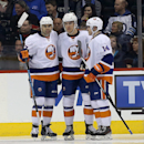 New York Islanders' Brian Strait (37), Anders Lee (27) and Thomas Hickey (14) celebrate after Lee scored against the Winnipeg Jets during the second period of an NHL hockey game in Winnipeg, Manitoba, Tuesday, March 4, 2014 The Associated Press