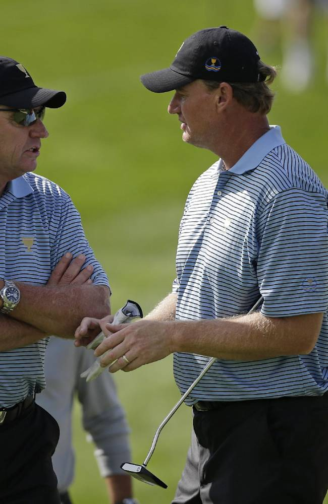 International team captain Nick Price talks with team player Ernie Els, of South Africa, on the 18th green during a practice round for the Presidents Cup golf tournament at Muirfield Village Golf Club Tuesday, Oct. 1, 2013, in Dublin, Ohio