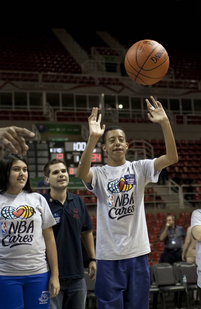 Washington Wizards forward Nene, left, instructs kids at a NBA Cares basketball clinic, in Rio de Janeiro, Brazil, Thursday, Oct. 10, 2013. The Wizards are in Brazil preparing for NBA's first exhibition game in South America against the Chicago Bulls on Saturday
