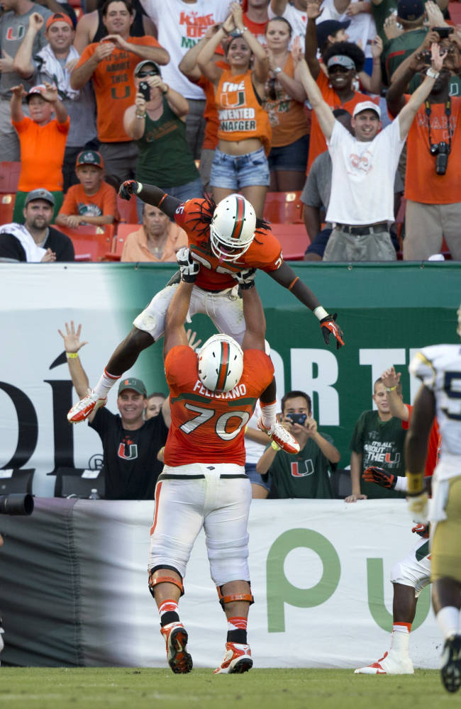 Miami players Jon Feliciano (70) and Dallas Crawford celebrate after Crawford scored a touchdown against Georgia Tech during the second half of an NCAA college football game in Miami Gardens, Fla., Saturday, Oct. 5, 2013. Miami won 45-30