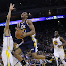 Utah Jazz guard Alec Burks, center, goes up for a shot next to Golden State Warriors forward Andre Iguodala, left, during the second half of an NBA basketball game Sunday, April 6, 2014, in Oakland, Calif. Golden State won 130-102 The Associated Press