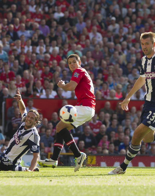 West Bromwich Albion's Jonas Olsson, bottom left, clears the ball away from Manchester United's Javier Hernandez, centre, as Gareth McAuley, right, looks on during their English Premier League soccer match at Old Trafford Stadium, Manchester, England, Saturday Sept. 28, 2013