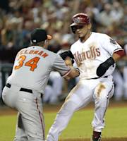 Baltimore Orioles pitcher Scott Feldman (34) applies the tag on Arizona Diamondbacks' Gerardo Parra at home plate during the second inning of a baseball game, Monday, Aug. 12, 2013, in Phoenix. Parra was ruled safe at the plate due to interference by third baseman Manny Machado while Parra was rounding third. (AP Photo/Matt York)