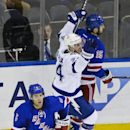 Tampa Bay Lightning's Ryan Callahan (24) celebrates as he skates past New York Rangers' Dan Girardi (5) and Tanner Glass (15) after scoring a goal during the third period of an NHL hockey game Monday, Nov. 17, 2014, in New York. The Lightning won the game 5-1. (AP Photo/Frank Franklin II)