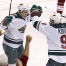 Minnesota Wild's Zach Parise (11) celebrates his empty-net goal against the Phoenix Coyotes with teammate Mikko Koivu (9), of Finland, during the third period of an NHL hockey game, Saturday, March 29, 2014, in Glendale, Ariz. The Wild defeated the Coyote