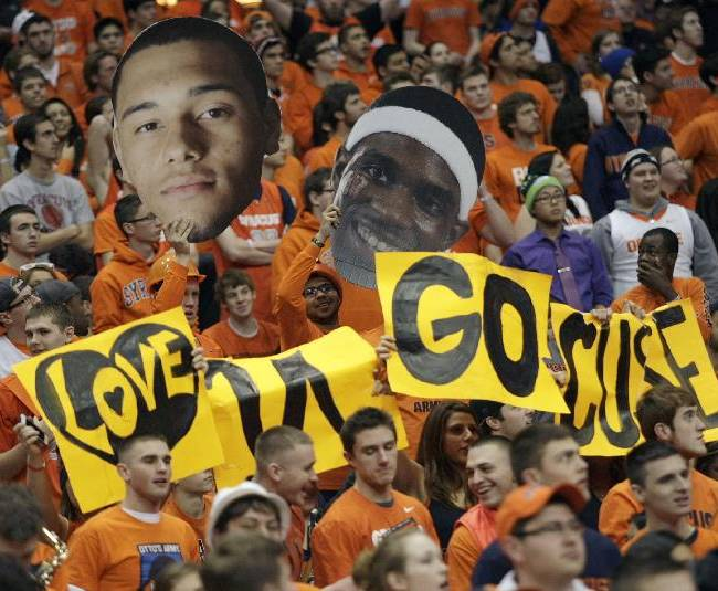 Syracuse fans cheer while waving cutouts of Syracuse players Tyler Ennis, left, and C.J. Fair, right, in the second half of an NCAA college basketball game against Pittsburgh in Syracuse, N.Y., Saturday, Jan. 18, 2014. Syracuse won 59-54