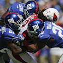 New York Giants cornerback Dominique Rodgers-Cromartie (21), Antrel Rolle (26) and Jon Beason (52) tackle Arizona Cardinals' Larry Fitzgerald (11) during the first half of an NFL football game Sunday, Sept. 14, 2014, in East Rutherford, N.J The Associated
