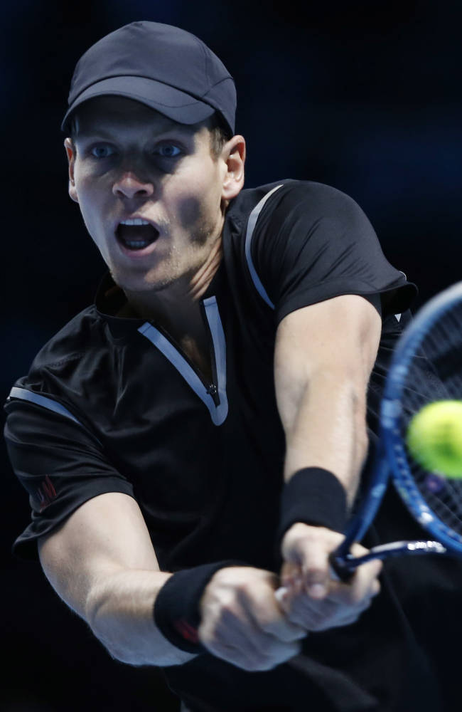 Tomas Berdych of Czech Republic plays a return to Stanislas Wawrinka of Switzerland during their ATP World Tour Finals single tennis match at the O2 Arena in London Monday, Nov. 4, 2013