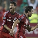 Toronto FC 's Andrew Wiedeman, right, celebrates scoring against New England Revolution as Toronto's Jonathan Osorio, left, looks on during first half of a MLS soccer game in Toronto on Friday Aug. 30, 2013. (AP Photo/The Canadian Press, Chris Young)