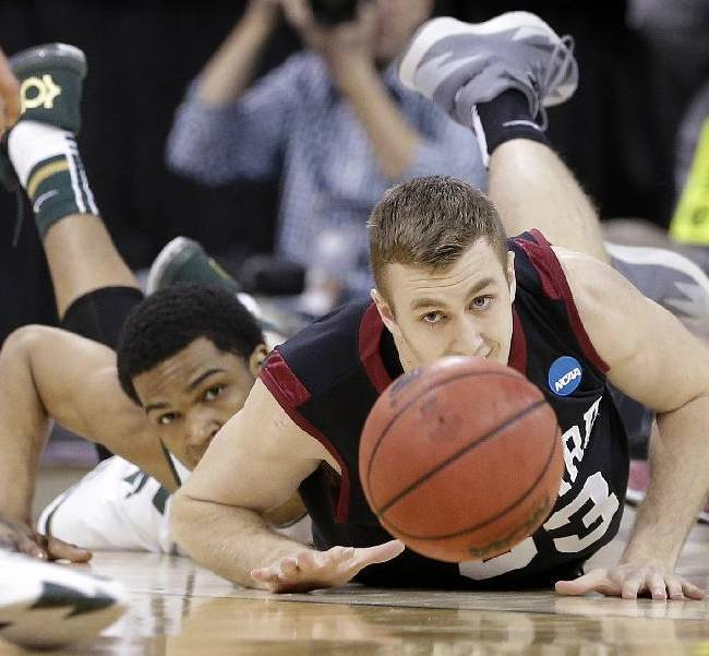 Harvard's Evan Cummins, right, and Michigan State's Alvin Ellis III eye a loose ball in the first half during the third round of the NCAA men's college basketball tournament in Spokane, Wash., Saturday, March 22, 2014