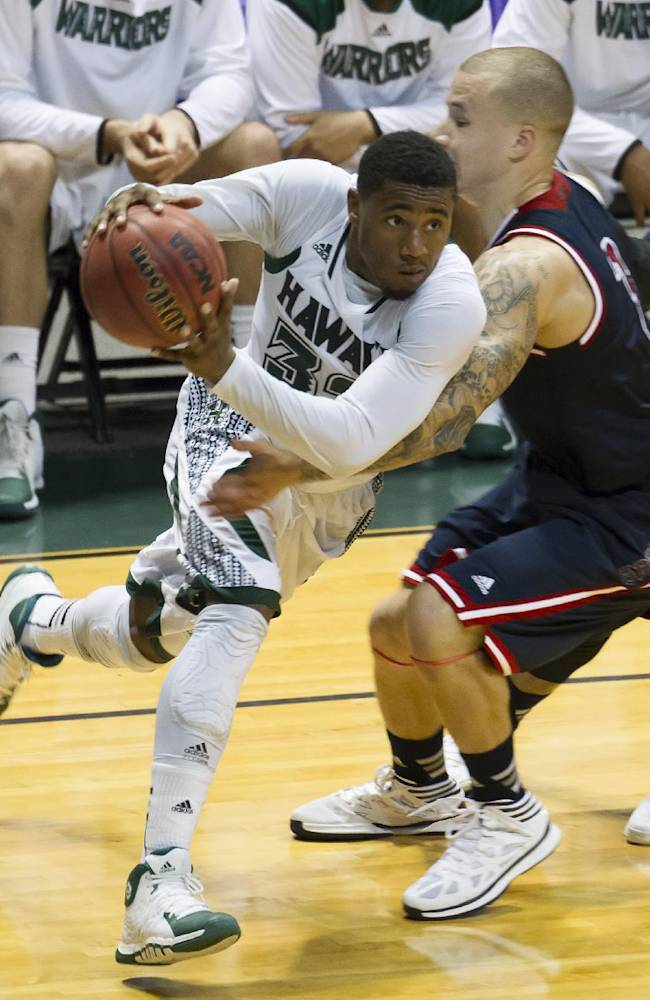 Hawaii guard Brandon Spearman, left, gets past St. Mary's guard Kerry Carter, right, and drives the baseline in the second half of an NCAA college basketball game at the Diamond Head Classic Monday, Dec. 23, 2013, in Honolulu. Hawaii beat Saint Mary's 76-74