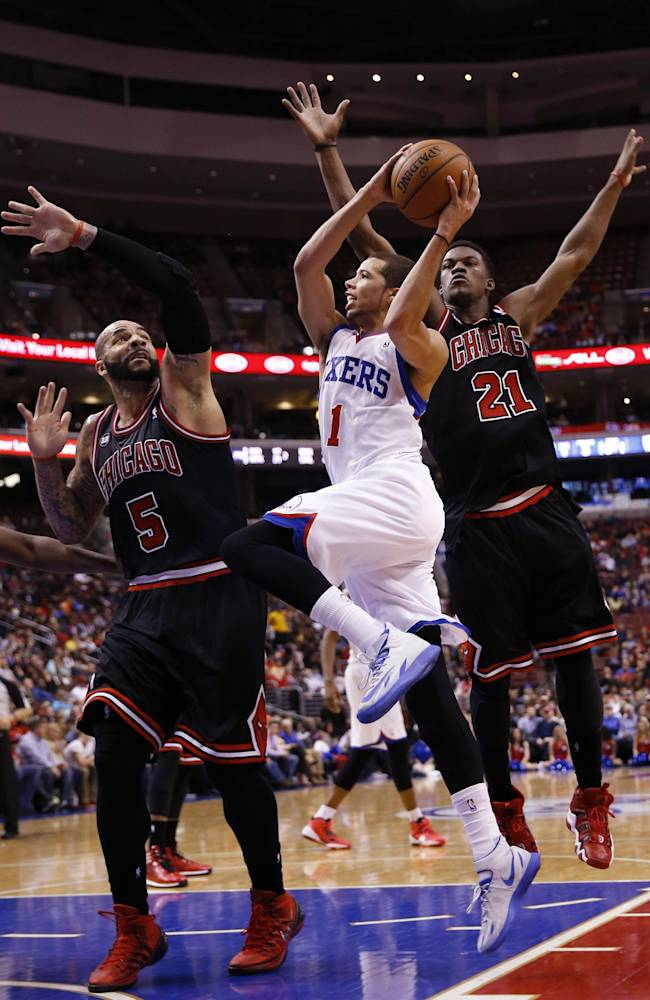 Philadelphia 76ers' Michael Carter-Williams, center, goes up for a shot against Chicago Bulls' Carlos Boozer, left, and Jimmy Butler during the second half of an NBA basketball game, Wednesday, March 19, 2014, in Philadelphia. Chicago won 102-94