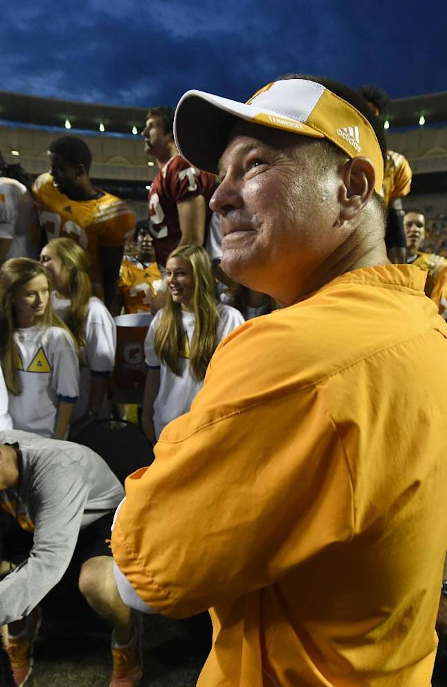 Tennessee coach Butch Jones, center, grins while looking up into the stands following Tennessee's open practice at Neyland Stadium in Knoxville on Saturday, Aug. 16, 2014