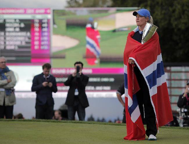 Suzann Pettersen of Norway looks on, draped in her national flag, as she holds her trophy after winning the Evian Championship women's golf tournament in Evian, eastern France, Sunday, Sept. 15, 2013