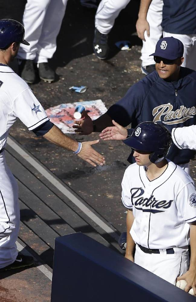 San Diego Padres' Tommy Medica (14) is greeted in the dugout after scoring when teammate Chris Denorfia was walked with the bases loaded by Pittsburgh Pirates starting pitcher Francisco Liriano during the fourth inning of a baseball game Wednesday, June 4, 2014, in San Diego