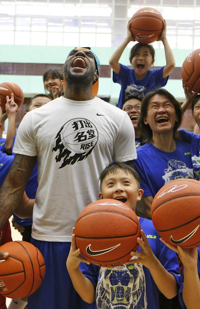NBA star LeBron James poses with his fans during a basketball clinic in Hong Kong as part of his China tour Wednesday, July 23, 2014. Earlier this month, James left the Miami Heat after four seasons and four trips to the NBA Finals and re-signed with the Cavaliers, where his career began. (AP Photo/Kin Cheung)
