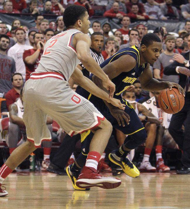 Michigan's Glenn Robinson, right, dribbles around Ohio State's Marc Loving during the first half of an NCAA college basketball game, Tuesday, Feb. 11, 2014, in Columbus, Ohio