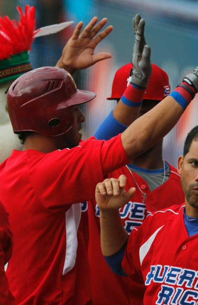 Puerto Rico outfielder Eddie Rosario, center, is congratulated by his teammates after he hit a solo home run against Cuba during their Caribbean Series baseball game in Porlamar, Venezuela, Tuesday, Feb. 4, 2014