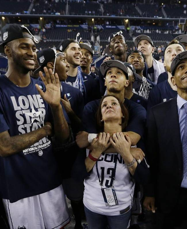 Connecticut guard Shabazz Napier, center embraces his mother, Carmen Velasquez as the team, including forward Phillip Nolan, left, and head coach Kevin Ollie, watches a highlight video of March Madness after their team beat Kentucky, 60-54 at the NCAA Final Four tournament college basketball championship game Monday, April 7, 2014, in Arlington, Texas