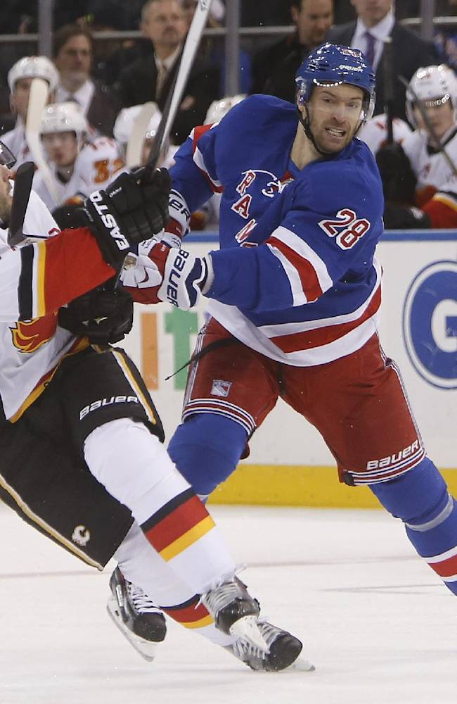 New York Rangers' Dominic Moore (28) collides with Calgary Flames' Lee Stempniak (22) during the first period of an NHL hockey game Sunday, Dec. 15, 2013, in New York