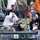 Baseball fans duck as the solo home run by Baltimore Orioles' Chris Davis clears the left field fence and the reach of Pittsburgh Pirates left fielder Starling Marte (6) during the third inning of a spring exhibition baseball game in Sarasota, Fla., Sunda