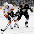 Los Angeles Kings left wing Dwight King (74) reaches in as Calgary Calgary Flames center Blair Jones (19) moves the puck up the ice during the first period of an NHL hockey game Saturday, Nov. 30, 2013, in Los Angeles The Associated Press