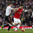 Arsenal's Mesut Ozil, right, competes with Liverpool's Steven Gerrard during their English FA Cup fifth round soccer match at Emirates Stadium in London, Sunday, Feb. 16, 2014