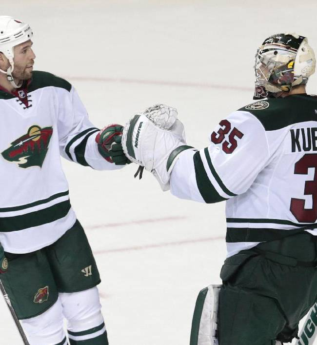 Minnesota Wild goalie Darcy Kuemper (35) is congratulated by Clayton Stoner (4) after Kuemper blocked 23 shots in a 4-0 win over the Nashville Predators in an NHL hockey game, Sunday, Jan. 12, 2014, in Nashville, Tenn