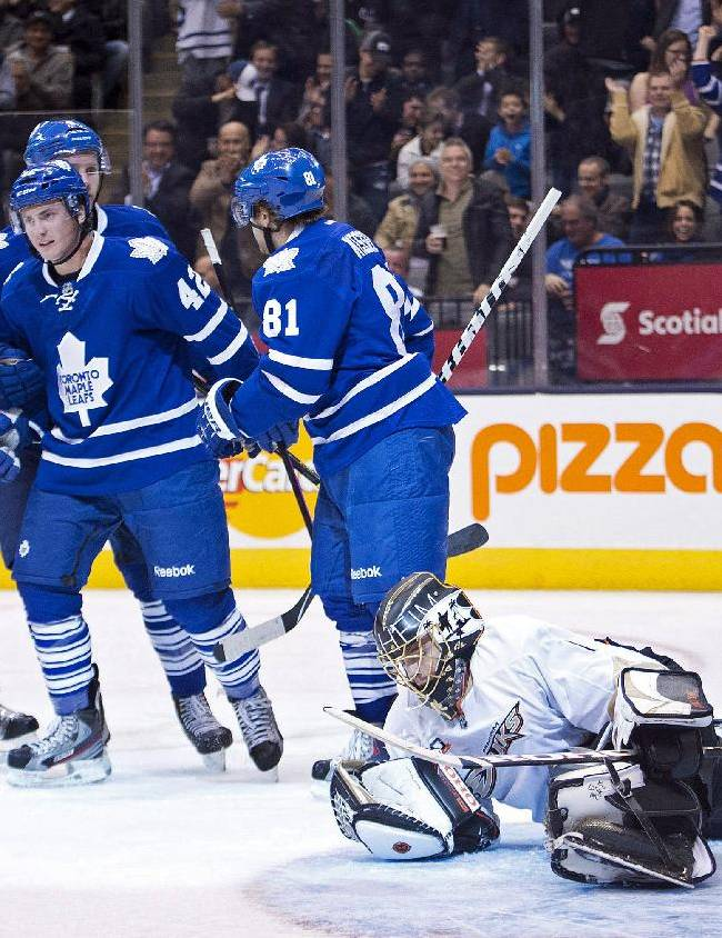 Toronto Maple Leafs players, from left, Dion Phaneuf, Cody Franson, Tyler Bozak, and Phil Kessel, celebrate Kessel's goal as Anaheim Ducks goalie Jonas Hiller, right, lays on the ice during the second period of an NHL hockey game in Toronto on Tuesday, Oct. 22, 2013