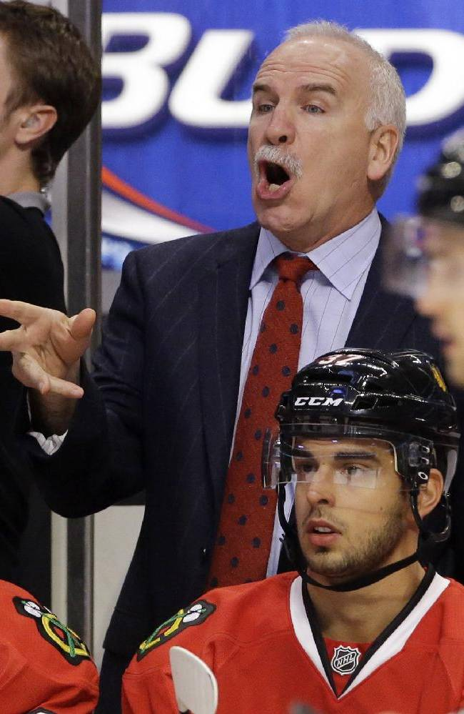 Chicago Blackhawks head coach Joel Quenneville directs his team during the first period of an NHL hockey game against the Minnesota Wild in Chicago, Saturday, Oct. 26, 2013